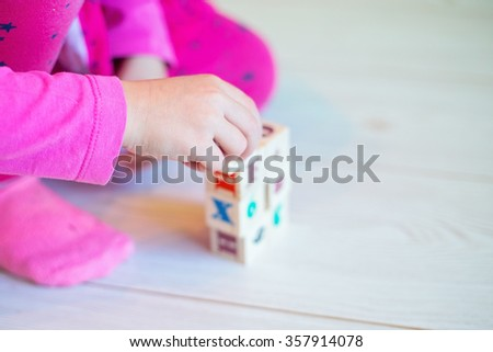 Baby's hand playing with wooden blocks