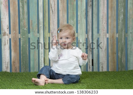 baby seated on grass in front of a weathered fence saying no