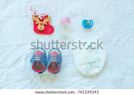 Baby set of item and accessories on white fabric background.