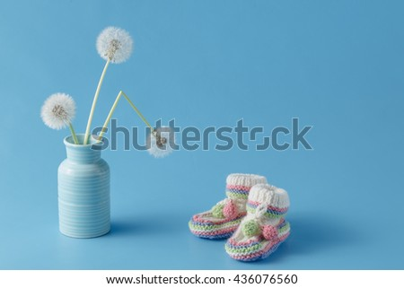 baby shower decoration on plain blue background with dandelions - stock photo