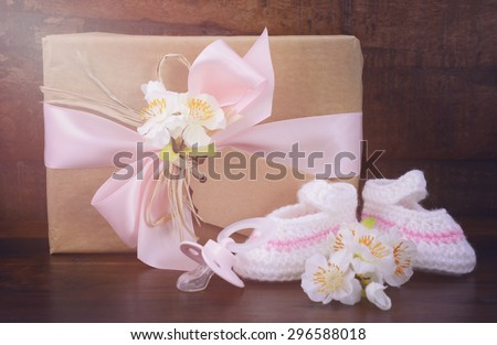 Baby Shower Gift with Booties and Pacifier on Rustic Dark Wood Background, with applied filters and added lens flare light stream.   - stock photo