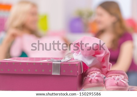 Baby shower. Young women showing baby clothes while gift box lying on foreground