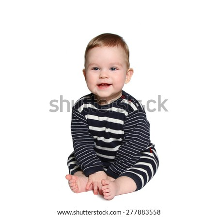 baby sits and laughs wearing blue and white striped clothes on white background - stock photo