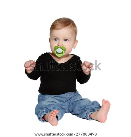 baby sits with green pacifier in mouth on white background - stock photo