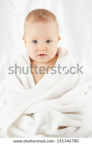 Baby sits wrapped in bath towel after bathing - stock photo