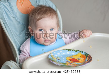 baby sitting Feeding table baby sitting in baby chair and eating Beautiful baby girl eating mashed. having healthy breakfast. eating fruit and dairy, sitting in a white sunny kitchen