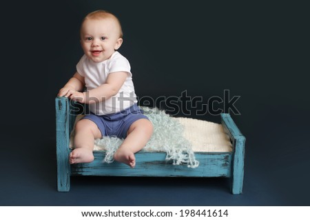Baby sitting in bed, happy and smiling; against a dark blue background. Nap time, sleeping concept - stock photo
