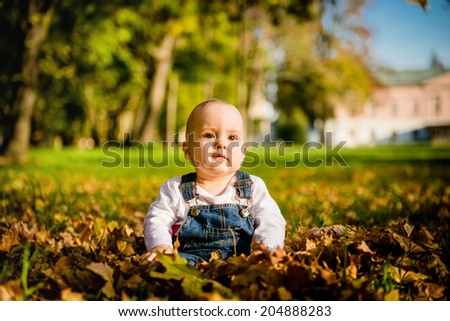 Baby sitting in fallen autumn leaves with unhappy thoughtful expression