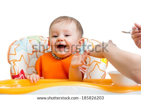 baby sitting in highchair and eating with a spoon