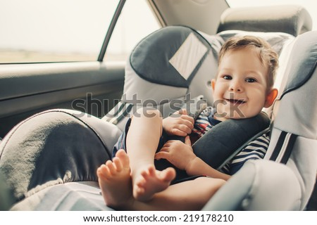 baby sitting in safety car seat - stock photo