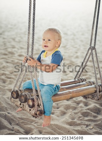 Baby sitting on a bamboo swing - stock photo