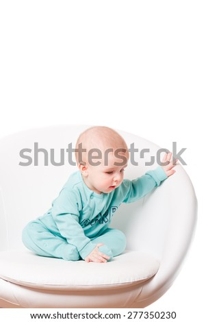 baby sitting on a white chair . Beautiful baby on a white background - stock photo