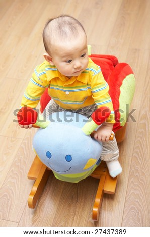 Baby sitting on animal rocking chair