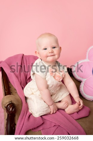 Baby sitting on couch with blanket, baby room and furniture concept - stock photo