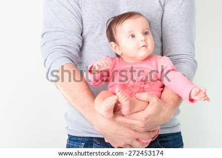 Baby sitting on father's hands. Baby is wearing pink body suit and looking at right side - stock photo