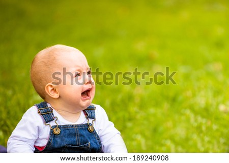 Baby sitting on grass and crying - outdoor with copy space - stock photo