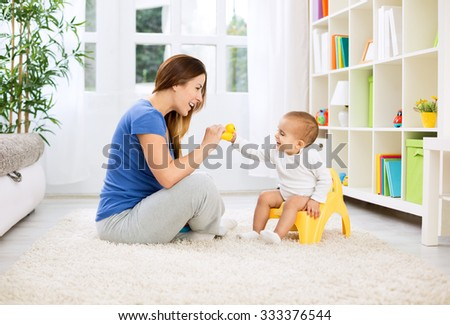 Baby sitting on potty and playing with smiling beautiful mother at home - stock photo