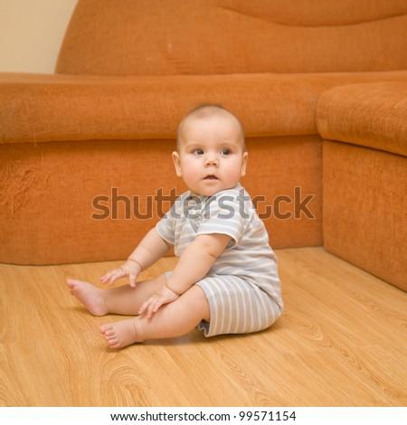 Baby sitting on the parquet floor near the orange sofa - stock photo