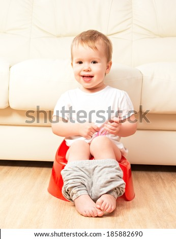 baby sitting on the potty in the toilet - stock photo