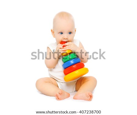Baby sitting playing with toys on a white background - stock photo