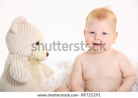 Baby sitting with teddy bear - stock photo