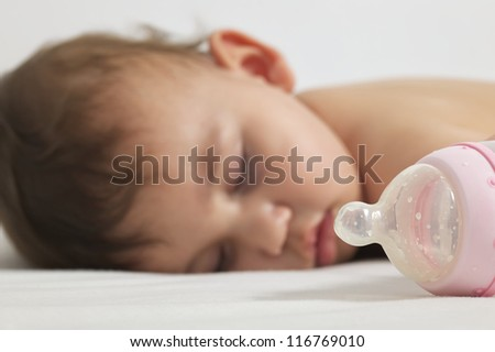 Baby sleeping after drinking here bottle milk - stock photo