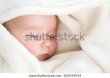 Baby sleeping covered with soft blanket - stock photo