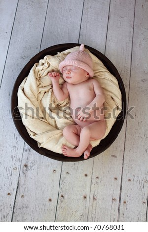Baby sleeping in a bowl - stock photo