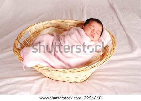 baby sleeping in basket - stock photo