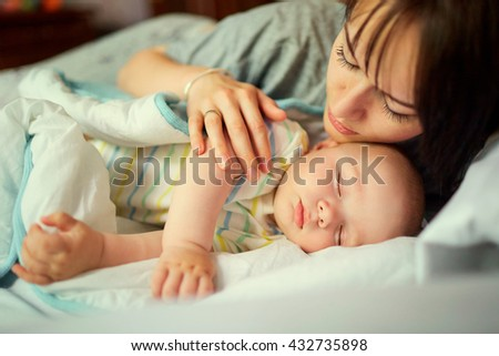Baby sleeping in bed with mother. Care. - stock photo