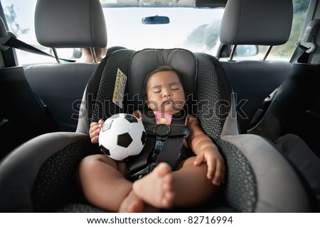 baby sleeping in car seat and holding a soccer ball - stock photo
