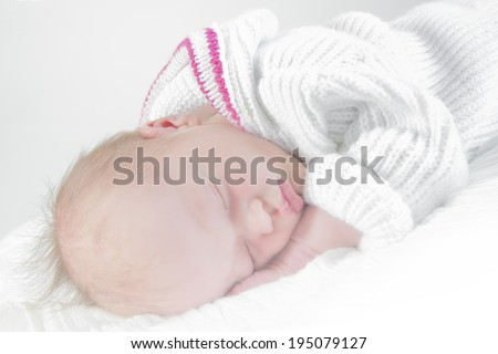 baby sleeping in white and pink clothes