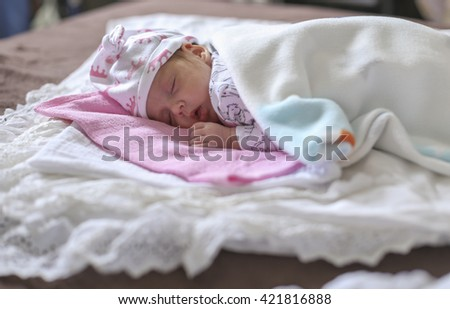 baby sleeping on a blanket in a funny hat - stock photo