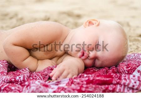 Baby sleeping on the sand - stock photo