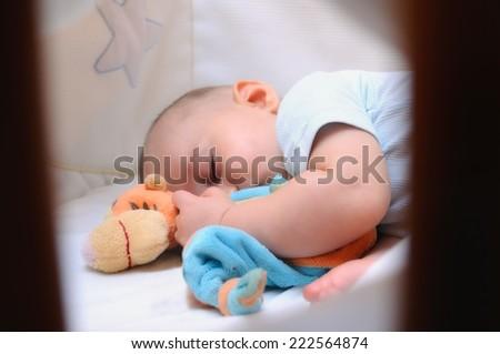 baby sleeping peacefully in his crib - stock photo