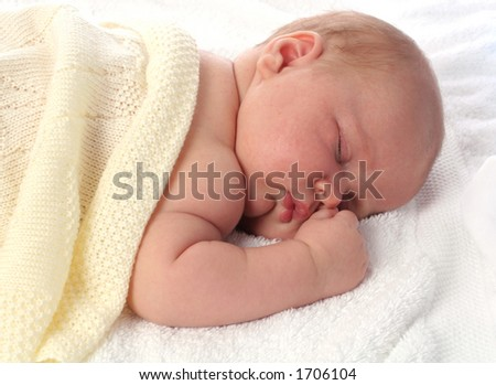Baby sleeping under knitted blanket