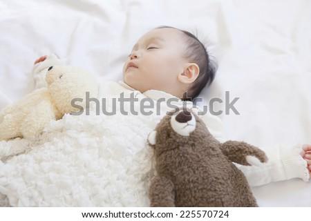 Baby sleeping with stuffed animals - stock photo