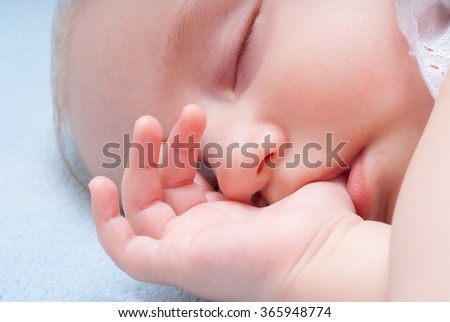 Baby sleeps with the finger in the mouth on a soft blue blanket, close up portrait - stock photo