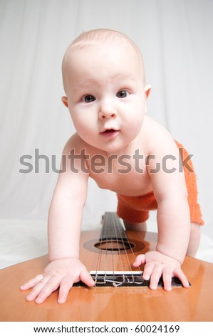 Baby smiles  and plays a guitar - stock photo