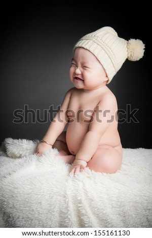 Baby smiling sitting on white blanket - stock photo