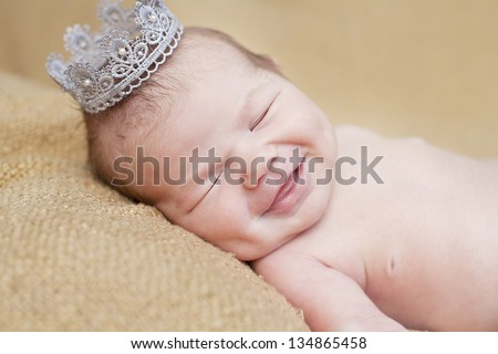 baby smiling with a crown - stock photo