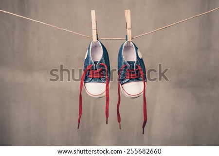 Baby sneakers hanging on the clothesline - stock photo
