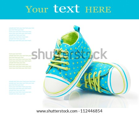 Baby sneakers on white with sample text - stock photo