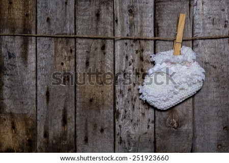 Baby sock with a clothespin on a wooden background - stock photo