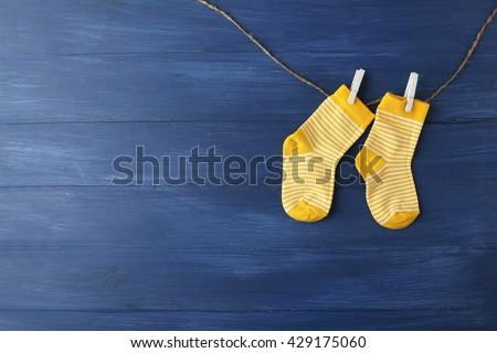 Baby socks hanging on dark blue background - stock photo