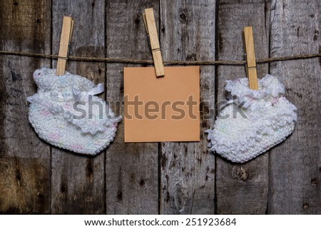Baby socks with a clothespin on a wooden background with colored paper for notes - stock photo