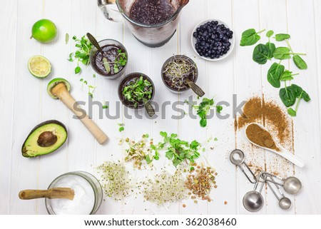 Baby spinach, blueberry cleaning smooth in a blender with ingredients ready to prepare smoothie bowl breakfast on white wooden table, rustic style - stock photo
