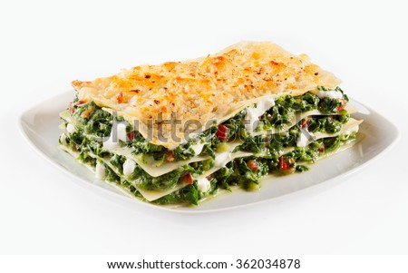 Baby spinach lasagne with mozzarella alternating with layers of traditional Italian noodles served on a square plate isolated on white - stock photo