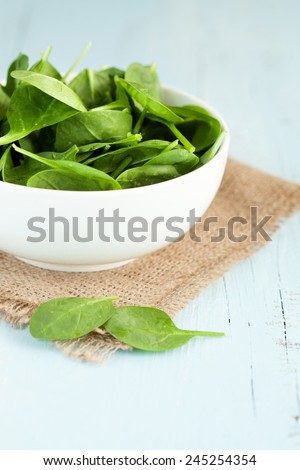 Baby spinach leaves in wooden bowl on blue background, selective focus - stock photo
