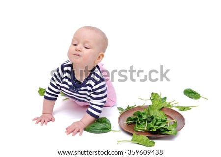 baby spinach studies/charming baby is exploring green spinach leaves; Isolated over White Background - stock photo